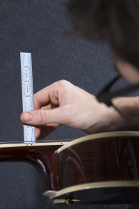 Guitar Tech Measuring the Action of an acoustic guitar with a ruler.