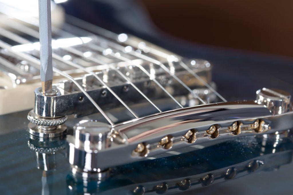 Screwdriver adjusting the bridge of a Les Paul Guitar